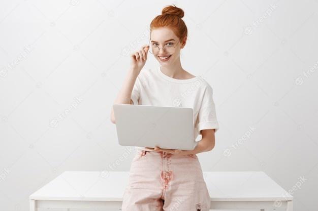 jovem-ruiva-trabalhando-com-laptop-e-usando-oculos_176420-21327